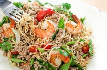 A plate of instant noodle salad with shrimp, tomatoes, and Chinese celery