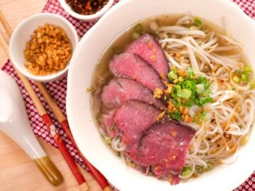 A bowl of beef noodle soup with fried garlic and chopsticks on the side.
