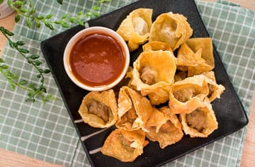 This Thai fried pork wonton recipe is a perfect make ahead appetizer: wrap them, fridge them, and fry when ready to eat! #wontons #pork #appetizer #fried #crispy #partyfood