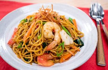 Mie goreng is a classic Indonesian dish that will please the family! Chewy egg noodles stir-fried in a sweet-salty sauce, with lot of crunchy veggies and juicy tomatoes. #easymeal #weeknightrecipe #eggnoodles #asianrecipe #indonesianfood