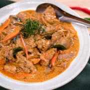 Panang is a popular classic Thai curry with a rich and luscious peanut sauce over tender beef that is super quick to make. I also share how to make semi-homemade panang curry paste using store-bought red curry paste as a base. An easy, delicious, gluten-free weeknight meal! #panangcurry #thaicurry #hotthaikitchen #Thairecipe #beefcurry