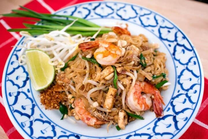 A plate of pad thai with shrimp and a side of lime and bean sprouts