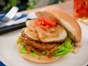 A plate of massaman burger with potatoes, onions and chilies.