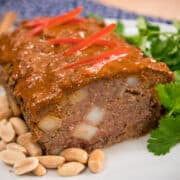 Massaman meatloaf on a plate with peanuts and cilantro garnish.
