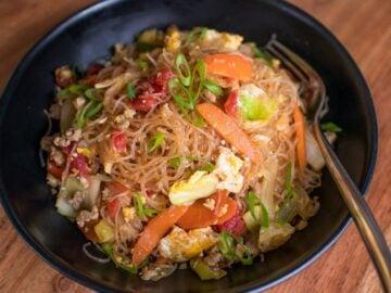 A black bowl of glass noodle stir fry.