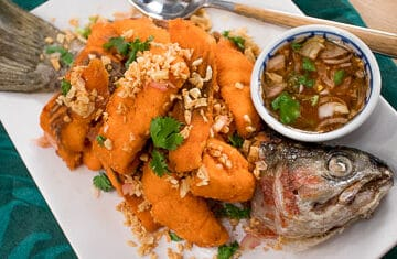 If you haven't cooked fish this way, it's a must-try! Fish fried in garlic oil, topped with crispy garlic and served with a tart spicy sauce. Perfect summer fish dish!
