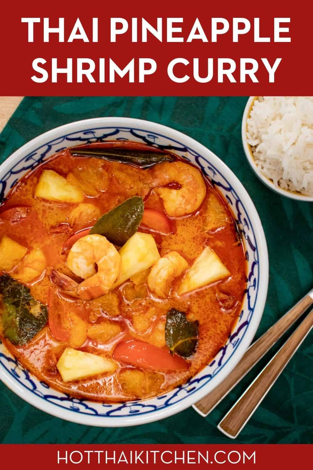 A Pinterest-friendly image of a bowl of red curry with shrimp and pineapple and a side of rice.