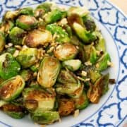 A plate of pan seared brussel sprouts with fried garlic on top.