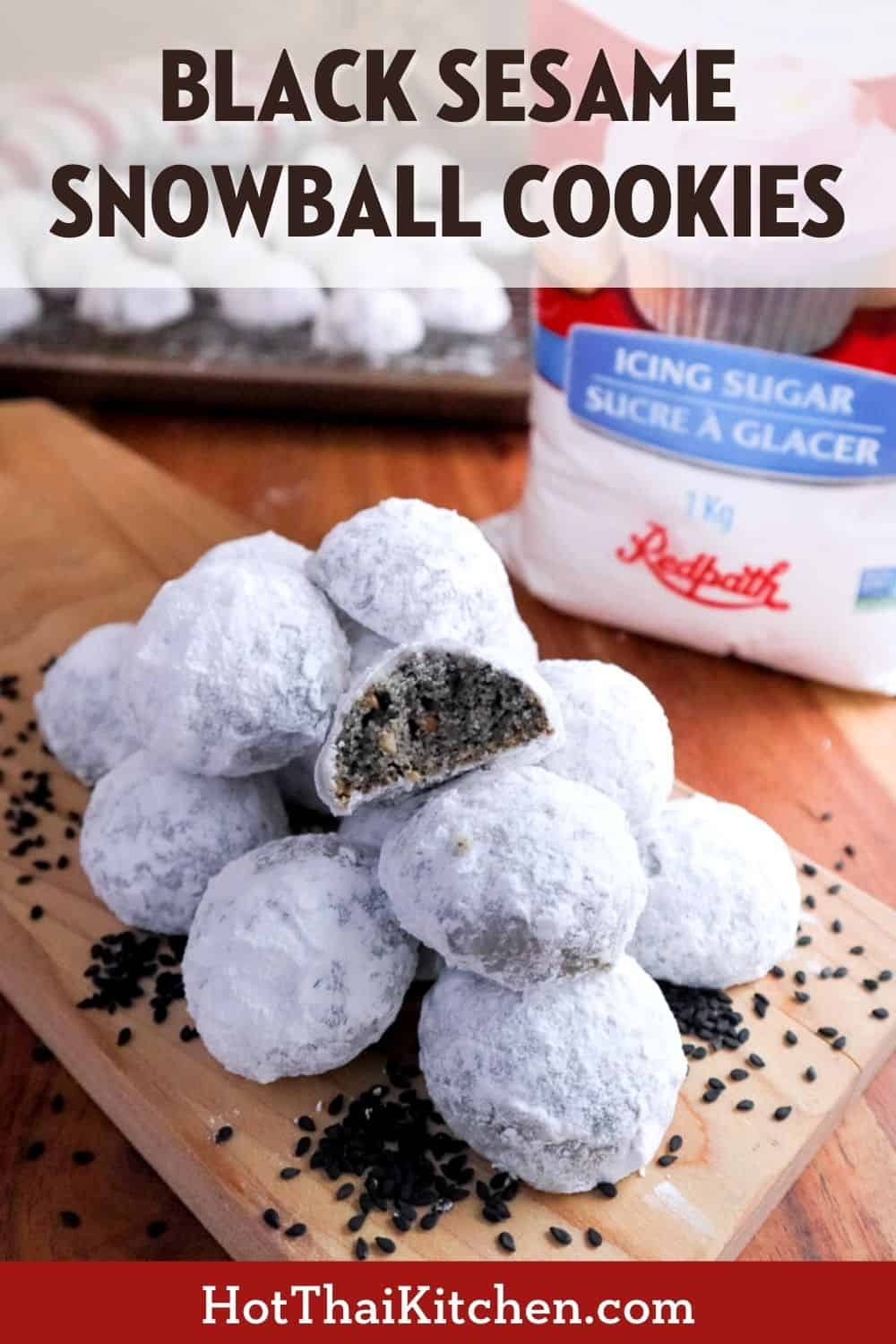 A pinterest-friendly image of a pile of black sesame snowball cookies on a cutting board, with one cookie cut open