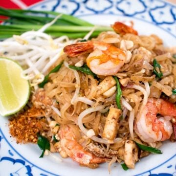 A plate of Pad Thai with shrimp, lime, chili flakes and beans sprouts