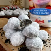 A pile of black sesame snowball cookies on a cutting board