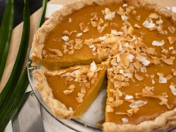 A whole pumpkin pie with one slice cut out with toasted coconut on top and pandan leaves on the side.