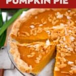 A pinterest-friendly image of a whole pumpkin pie with one slice cut out with toasted coconut on top and pandan leaves on the side.