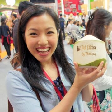 "Pic of pailin holding a young coconut engraved with ""hot thai kitchen"""