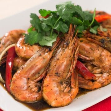 A plate of black pepper prawns with cilantro garnish
