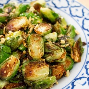 A plate of pan seared brussels sprouts with fried garlic