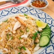 A plate of crab fried rice with cucumber and lime on the side, with a little bowl of fish sauce and chilies condiment