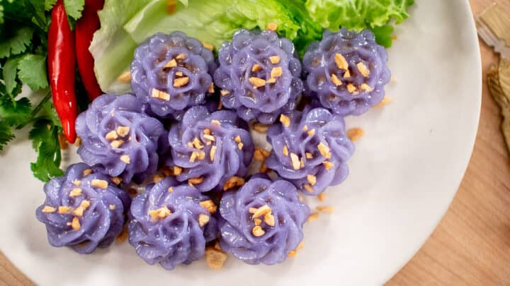 A plate of purple flower-shaped dumplings, with fried garlic on top, with a side of lettuce, chilies and cilantro.