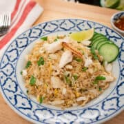 A plate of fried rice with crab, cucumber and lime.