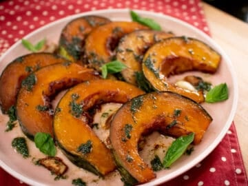 A plate of roasted kabocha squash wedges with basil leaves