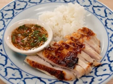 A plate of roasted turkey breast slices, sticky rice, and a bowl of Thai dipping sauce