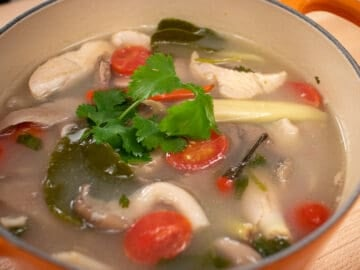 A pot of Thai soup with turkey, mushrooms, and tomatoes with cilantro on top
