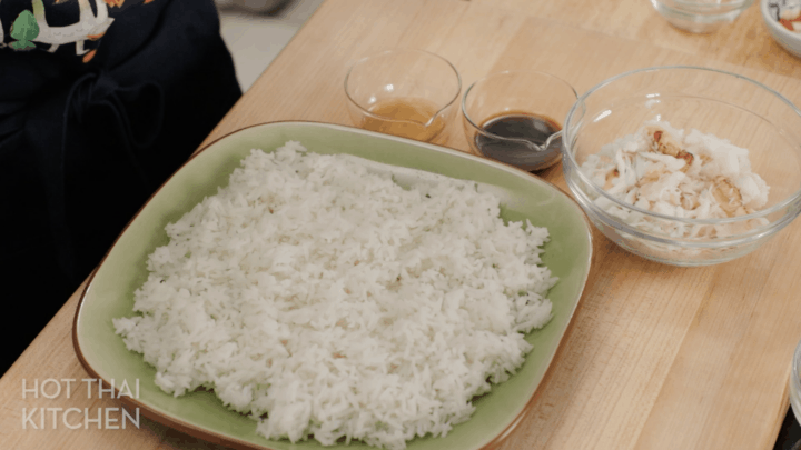 Rice spread out on a plate, with bowls of fish sauce and soy sauce beside it.