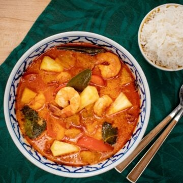 A bowl of pineapple shrimp curry with a side of rice