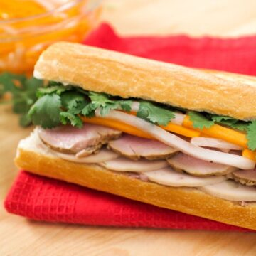 Banh mi sandwich with roast pork, pickled daikon and carrots, and cilantro.