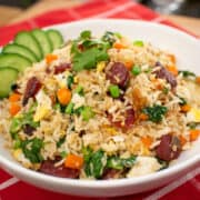 A bowl of chinese sausage fried rice with cucumber garnish on red table cloth