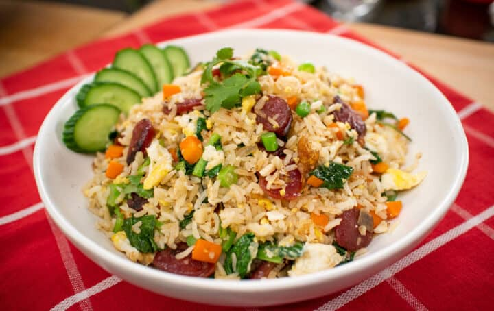 A bowl of chinese sausage fried rice with cucumber garnish on red tablecloth.
