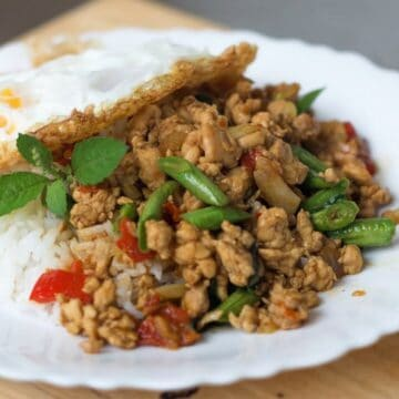 A plate of ground chicken stir fry with long beans and holy basil. With a fried egg on top.