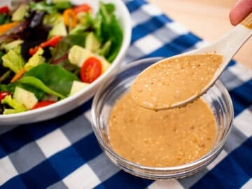A spoonful of roasted sesame dressing being held over a bowl of dressing. With a green salad on the side. sp