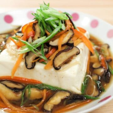 a plate of steamed tofu with shitake mushrooms, carrots topped with green onions