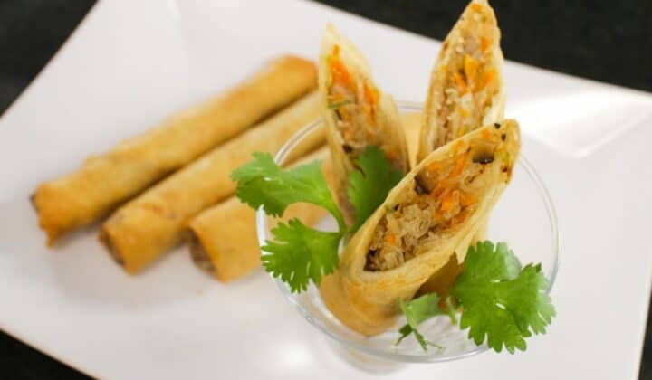 A plate of spring rolls, with 3 pieces cut open served in a glass. Cilantro garnish.