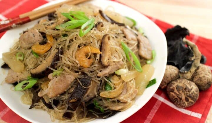 A bowl of glass noodle stir fry with dried shrimp, shiitake mushrooms and green onions on top.