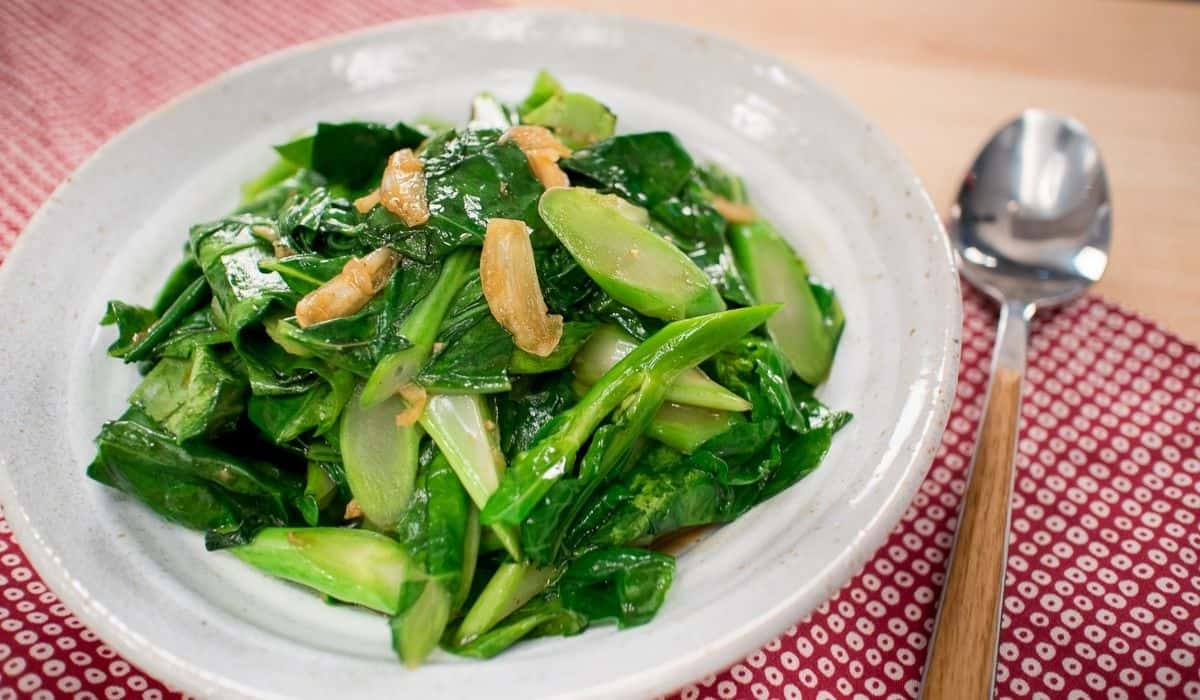A plate of chinese broccoli stir fry with garlic pieces on top