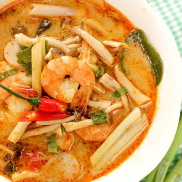 a bowl of tom yum soup with shrimp, mushrooms, lemongrass and chilies