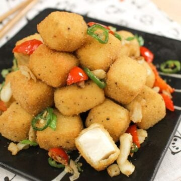 A plate of breaded a fried tofu bites with chilies and garlic