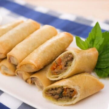 a plate of sprill rolls with one cut open, and a thai basil garnish