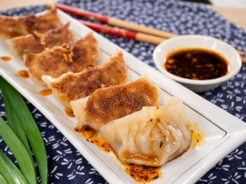 A plate of gyozas with crispy bottoms, with chili oil drizzled on them and dipping sauce on the side.