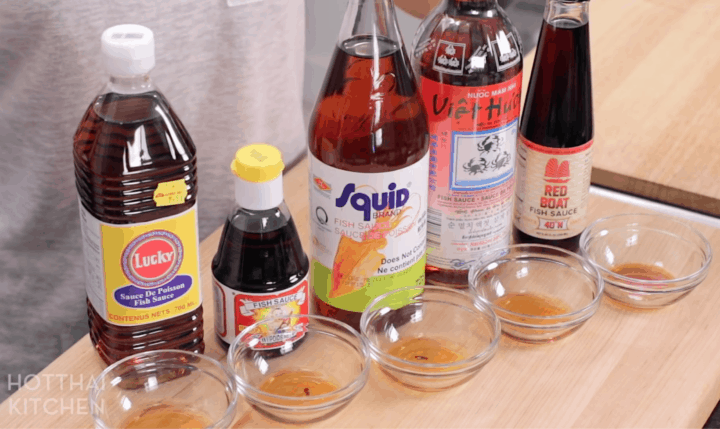 A line up of 5 different brands of fish sauce: Lucky, Golden Boy, Squid, 3 Crabs, and Red Boat