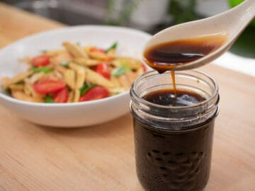 Stir fry sauce in a mason jar with a spoon pouring sauce into it. With a plate of a veggie stir fry in the background