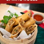 A Pinterest image of spring rolls cut in half in a steamer basket.