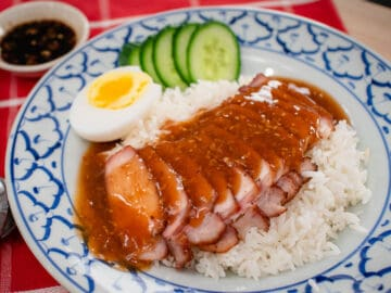 A plate of Chinese BBQ pork on rice with gravy on top. With a side of medium boiled egg and cucumber slices and a bowl of soy chili vinegar dippins sauce.