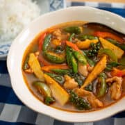 A bowl of jungle curry with baby corn, Thai eggplant, long beans, and chicken, with a plate of jasmine rice on the side.