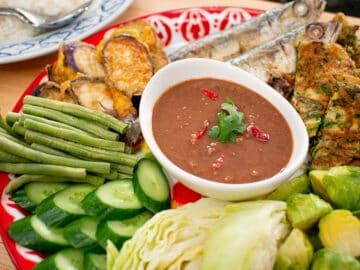 A platter of shrimp paste dip with fresh veggies, omelette, and mackerel.