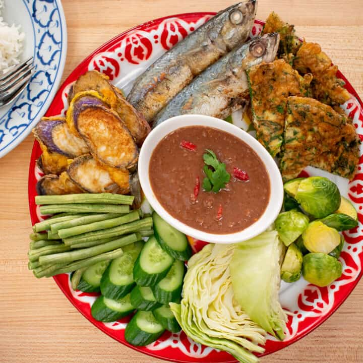 A platter of shrimp paste dip with steamed and raw veggies, omelette, and pan fried mackerel.