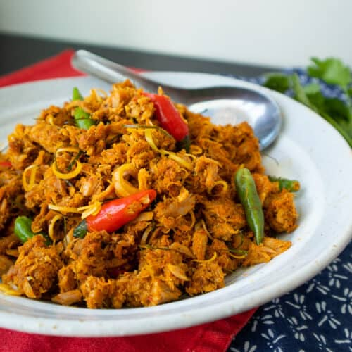 A plate of tuna stir fried in red curry with red and green chilies.