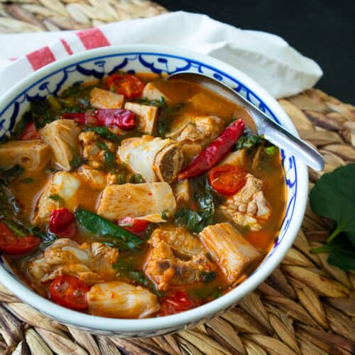 A bowl of ribs and jackfruit curry with chilies, tomatoes, and greens.